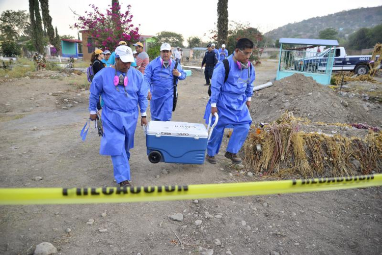 Specialists in Jojutla, Mexico, unearth remains found in unmarked graves on March 21. (CNS photo/Tony Rivera, EPA)