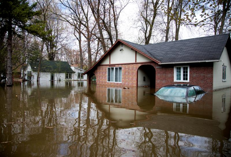 A car is seen submerged in front of a home on May 9 in the flooded Montreal suburb of Pierrefonds, Quebec. A mix of heavy rains and melting snow caused the situation. (CNS photo/Christinne Muschi, Reuters)