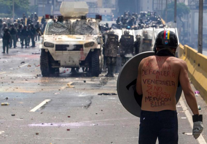 A protester faces the National Guard during clashes on May 10 in Caracas, Venezuela.  (CNS photo/Miguel Guitierrez, EPA)