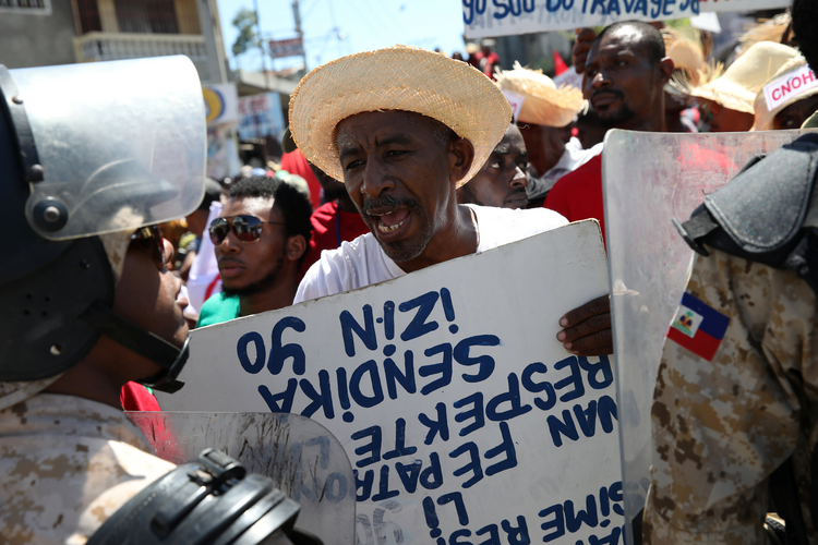 A man argues with a Haitian National Police officer on March 1 as a police line blocks a street during a march calling for better labor conditions in Port-au-Prince. (CNS photo/Andres Martinez Casares, Reuters)