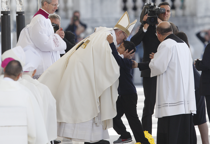 Pope Francis embraces Lucas Batista from Brazil as offertory gifts are presented during the canonization Mass of Sts. Francisco and Jacinta Marto.