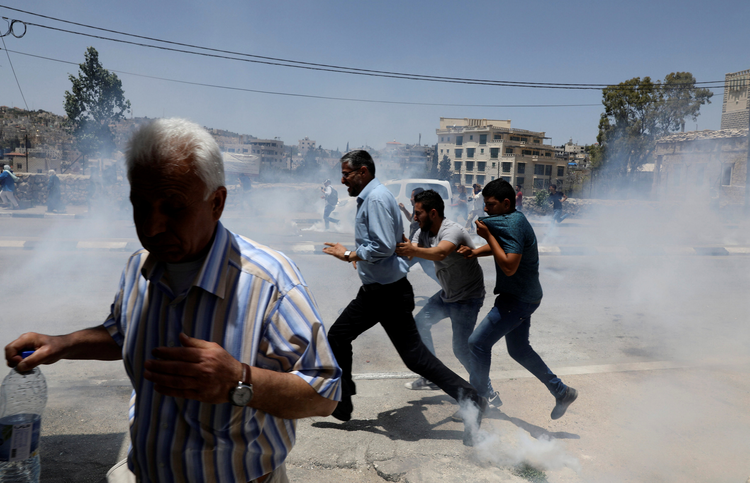 "Palestinian protesters run for cover from tear gas fired by Israeli troops in clashes on May 15 during a protest in the West Bank town of Bethlehem marking the 69th anniversary of their uprooting. Palestinians call the 1948 uprooting ""nakba"" or catastrophe. (CNS photo/Ammar Awad, Reuters)"