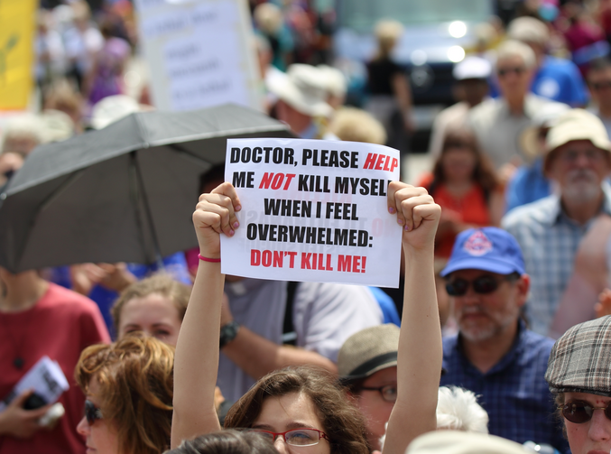 A woman holds up a sign during a rally against assisted suicide in 2016 on Parliament Hill in Ottawa, Ontario. (CNS photo/Art Babych)