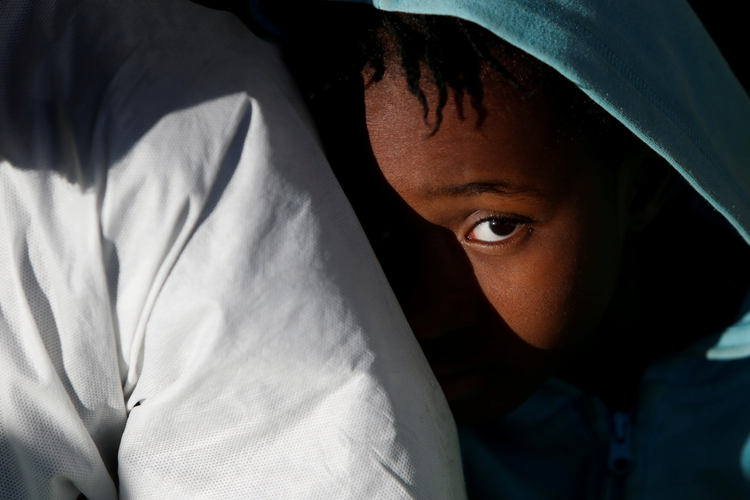 A migrant child sits on the deck of rescue ship as it arrives on April 19 in Augusta, Italy. (CNS photo/Darrin Zammit Lupi, pool via Reuters)