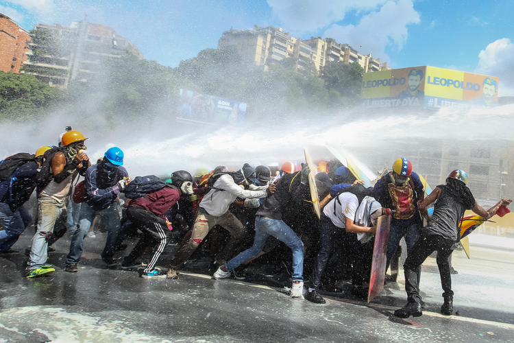 Government protestors in Caracas, Venezuela, are sprayed by a national guard water canon May 29. (CNS photo/Mauricio Duenas, EPA)