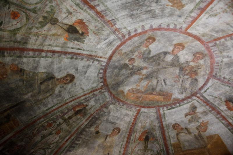 A fresco showing Noah releasing doves, lower right, and other scenes representing salvation are seen during the unveiling of two newly restored burial chambers in the Christian catacombs of St. Domitilla in Rome on May 30. (CNS photo/Carol Glatz)