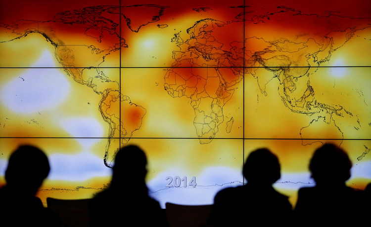 Participants look at a screen showing a world map with climate anomalies during the World Climate Change Conference at Le Bourge, France, in this Dec. 8, 2015, file photo. (CNS photo/Stephane Mahe, Reuters)