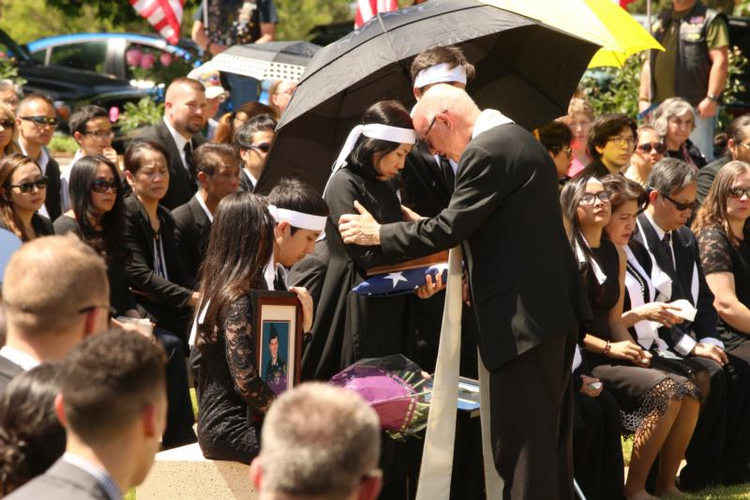 Msgr. Richard Paperini comforts Myhanh Best, wife of Ricky Best, who was killed on a Portland, Ore., commuter train on May 26 while defending two girls from an anti-Muslim racist attack. (CNS photo/Ed Langlois, Catholic Sentinel)