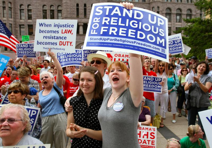 People display signs showing their support for religious freedom during a 2012 rally in downtown Minneapolis. It has been 20 years since the International Religious Freedom Act was passed by Congress and became law. (CNS photo/Dave Hrbacek, The Catholic Spirit)