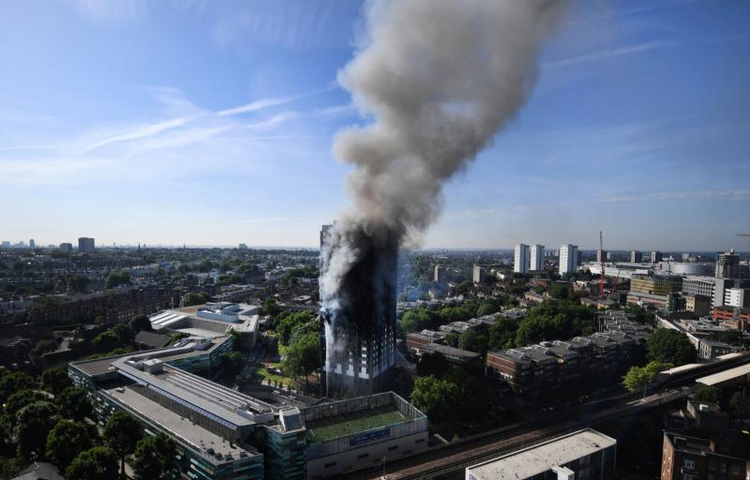 Flames and smoke billow from a London apartment building on June 14. London's Metropolitan Police said a number of people were being treated for a range of injuries, and authorities appealed for families to report anyone unaccounted for. (CNS photo/Andy Rain, EPA)