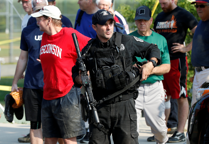 A U.S. Capitol police SWAT team officer escorts members of Congress and congressional staff from the scene after a gunman opened fire on Republican members of Congress during a baseball practice in Alexandria, Va., on June 14. (CNS photo/Joshua Roberts, Reuters)