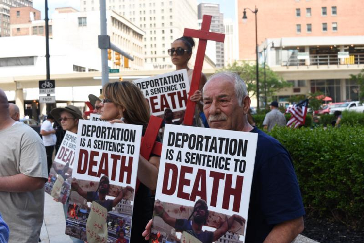 Members of the local Chaldean community gather outside the Patrick V. McNamara Federal Building on June 16 to protest the arrest and detention of more than 100 Chaldean Christians from the Detroit area. (CNS photo/Dan Meloy, The Michigan Catholic)