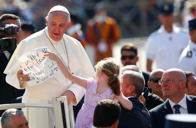 Pope Francis receives a letter from a girl as he arrives for his general audience on June 21 in St. Peter's Square at the Vatican. (CNS photo/Tony Gentile, Reuters)