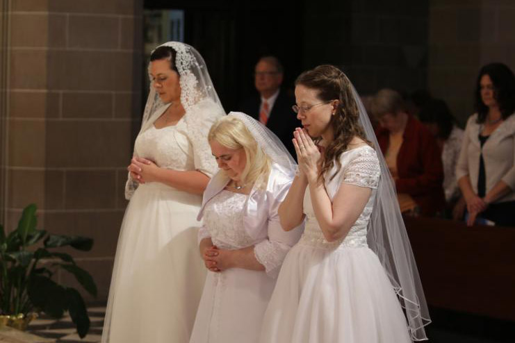 Karen Ervin, Theresa Jordan and Laurie Malashanko pause in prayer before the altar at the Cathedral of the Most Blessed Sacrament in Detroit on June 24. They were consecrated into the Catholic Church's order of virgins. (CNS photo/Joel Breidenbach)