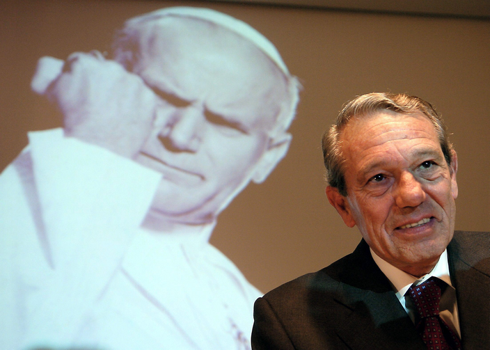 Joaquin Navarro-Valls, who spent 22 years as director of the Vatican press office, died on July 5 at age 80. He is pictured speaking in 2004 alongside a projected image of St. John Paul II. (CNS photo/Arne Dedert, EPA)