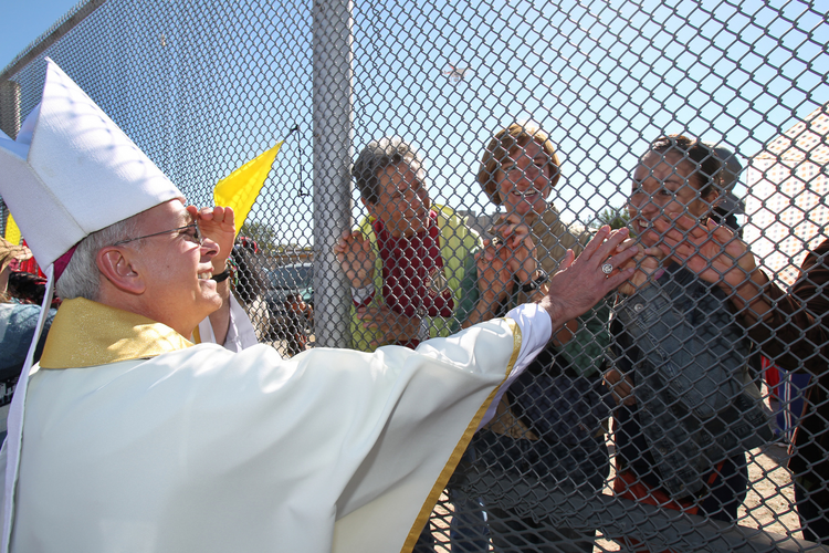 Bishop Mark J. Seitz of El Paso, Texas, touches the hands of people in Mexico through a border fence following Mass in Sunland Park, N.M., in this 2014 file photo. (CNS photo/Bob Roller)
