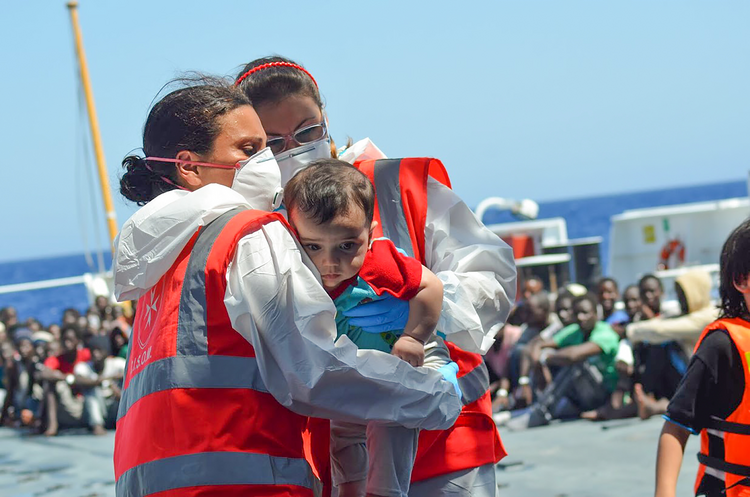 Volunteers of the Order of Malta's Italian Relief Corps provide assistant to an infant rescued in the Mediterranean Sea. (CNS photo/courtesy CISOM)