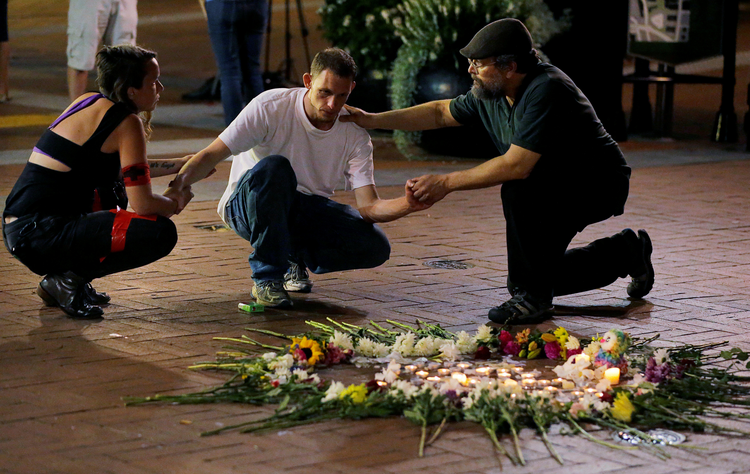 Two people comfort Joseph Culver of Charlottesville, Va., Aug. 12 as he kneels at a late night vigil to pay his respects for a friend injured in a car attack on counter-protesters rallying against white nationalists. (CNS photo/Jim Bourg, Reuters)