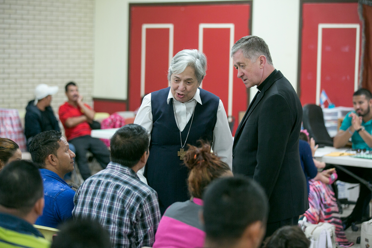 Sister Norma Pimentel, executive director of Catholic Charities of the Rio Grande Valley, and Cardinal Blase J. Cupich of Chicago greet asylum seekers at the Humanitarian Respite Center at Sacred Heart Church in McAllen, Texas, on Aug. 15. (CNS photo/courtesy Catholic Extension)