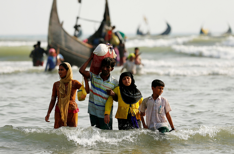 Rohingya refugees walk to shore in Teknaf, Bangladesh, with their belongings after crossing the Bangladesh-Myanmar border through the Bay of Bengal on Sept. 5. (CNS photo/Mohammad Ponir Hossain, Reuters)