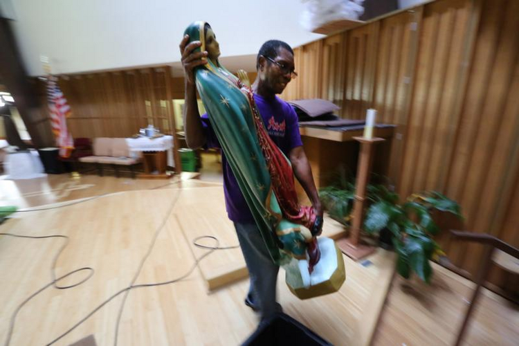 Father Martin Eke, pastor of St. Francis of Assisi Church in Houston, recovers a statue of Our Lady of Guadalupe on Sept. 6 that was severely damaged from the floodwaters of Tropical Storm Harvey. The parish is home to a large African-American community in the Archdiocese of Galveston-Houston. (CNS photo/Bob Roller)