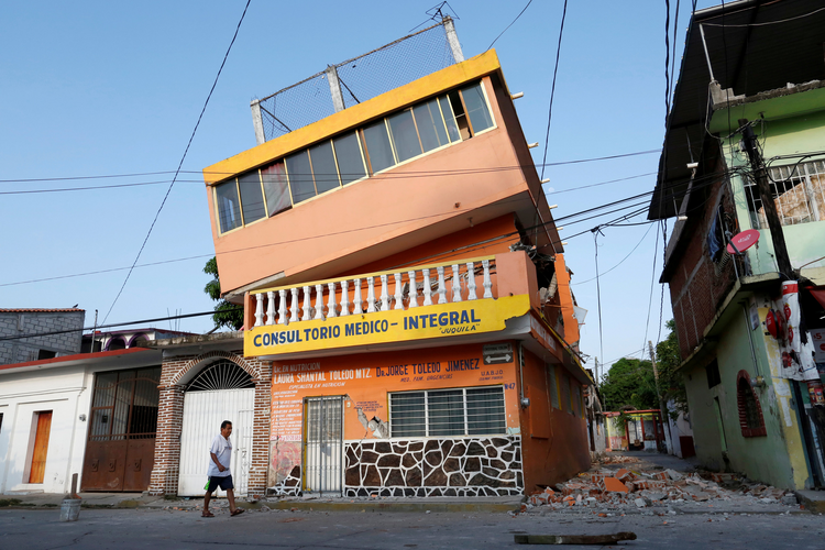 A man walks next to an earthquake-damaged building in Juchitan, Mexico, on Sept. 9. (CNS photo/Carlos Jasso, Reuters)