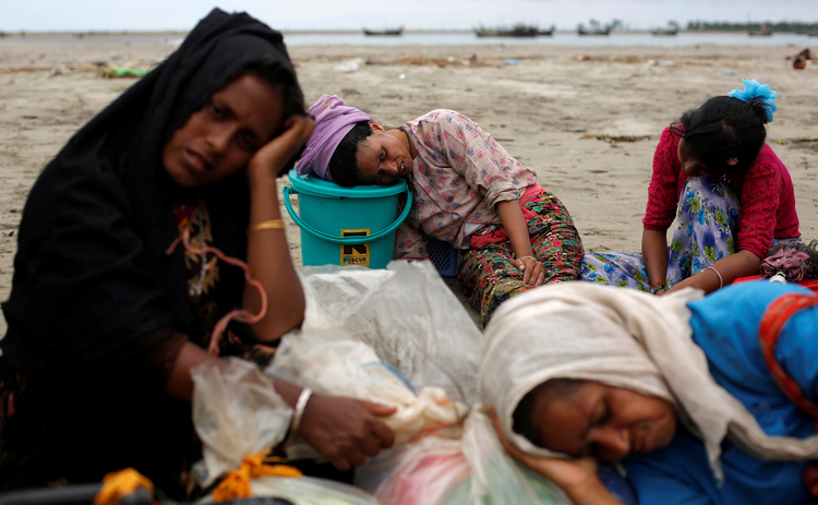Exhausted Rohingya refugees rest on the shore in Shah Porir Dwip, Bangladesh, after crossing by boat through the Bay of Bengal on Sept. 10. (CNS photo/Danish Siddiqui, Reuters)