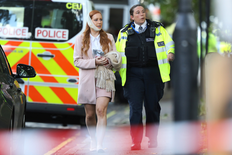 An injured woman is led away following a blast caused by an improvised explosive device on a London Underground train Sept. 15. The blast injured more than a dozen people and is being treated as terrorism by police investigators. (CNS photo/Luke MacGregor, Reuters)