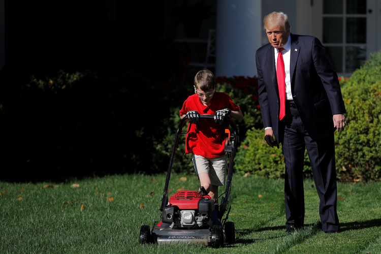 U.S President Donald Trump looks on as Frank Giaccio, an altar server at St. James Church in Falls Church, Va., mows the Rose Garden lawn on Sept. 15 at the White House in Washington. The 11-year-old, who wrote a letter to Trump offering to mow the White House lawn, was invited to work for a day at the White House. (CNS photo/Carlos Barria, Reuters)