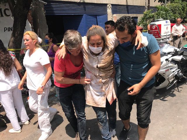An injured woman is assisted in Mexico City on Sept. 19 after a magnitude 7.1 earthquake hit to the southeast of the city, killing hundreds. (CNS photo/Carlos Jasso, Reuters)