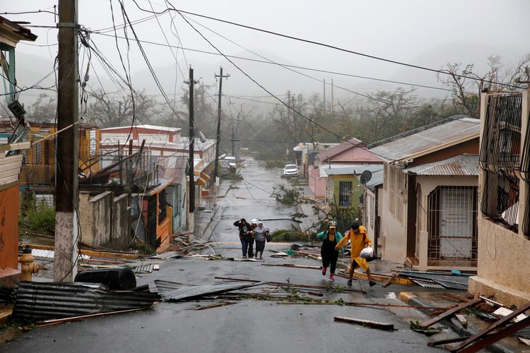 "Rescue workers help people on Sept. 20 in Guayama, Puerto Rico, after the area was hit by Hurricane Maria. After battering the Virgin Islands, the hurricane made landfall in Puerto Rico, bringing ""catastrophic"" 155 mph winds and dangerous storm surges. (CNS photo/Carlos Garcia Rawlins, Reuters)"