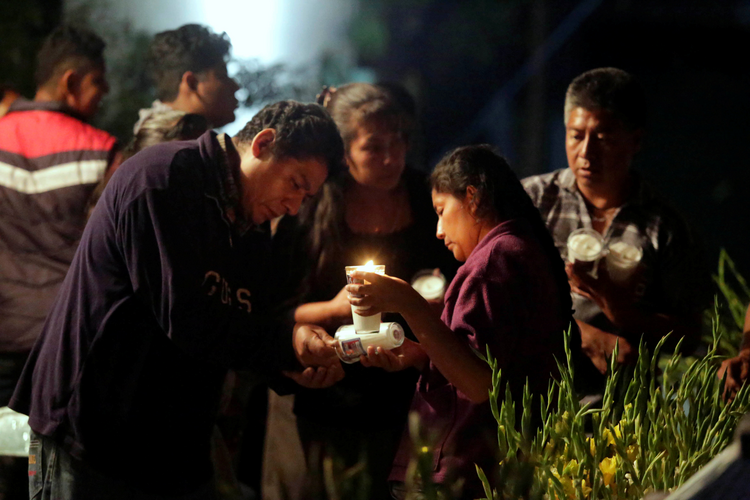 People light candles on Sept. 20 for the 11 victims who died after the roof of a church collapsed following an earthquake in Atzala, on the outskirts of Puebla, Mexico. A Catholic bishop and a Caritas worker in Mexico said the situation was extremely serious after the Sept. 19 earthquake, and much aid would be needed. (CNS photo/Imelda Medina, Reuters)
