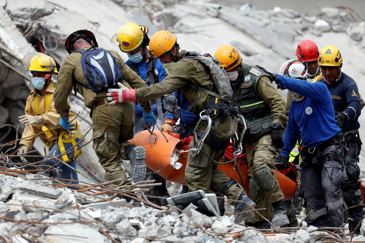 Members of Israeli and Mexican rescue teams carry a body from a collapsed building in Mexico City on Sept. 21, two days after an earthquake. (CNS photo/Carlos Jasso, Reuters)