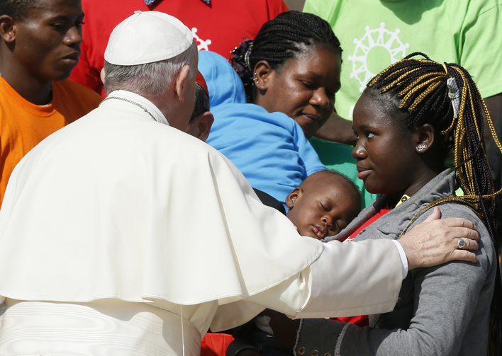 Pope Francis greets immigrants and representatives of Caritas Internationalis during his general audience in St. Peter's Square at the Vatican Sept. 27. (CNS photo/Paul Haring)