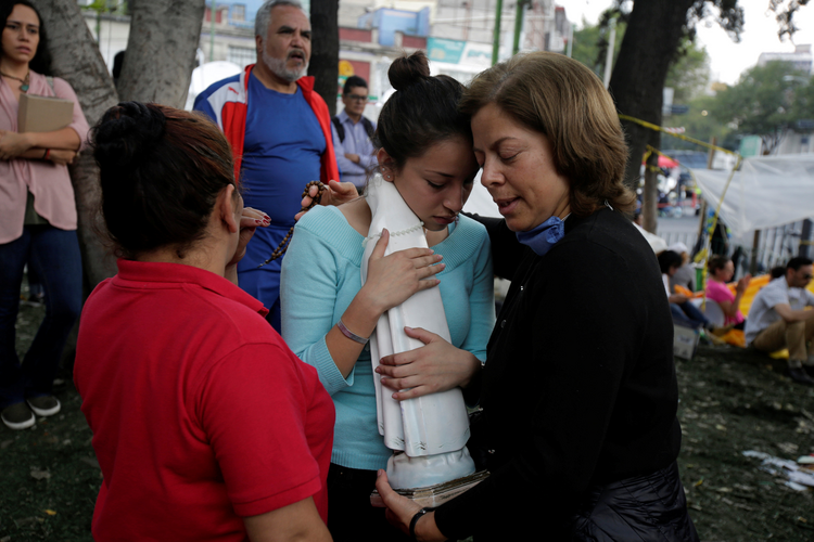 A young woman holding a statue of Mary is comforted by family members of a person trapped in the rubble of a collapsed building on Sept. 26 in Mexico City. Five days after the deadly magnitude 7.1 earthquake, the collapsed seven-story office building is one of the last hopes searchers believe they may still find someone trapped alive. (CNS photo/Jose Luis Gonzalez, Reuters)