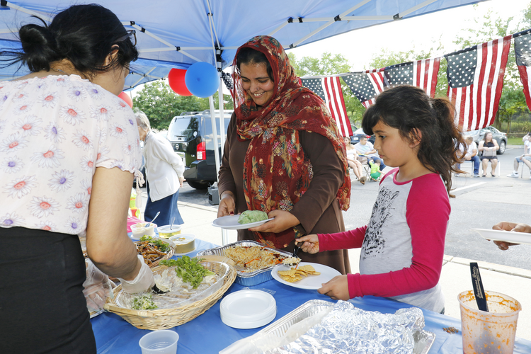 A Pakistani woman and her daughter stand in a buffet line during a Catholic Charities-hosted party for refugees held in observance of World Refugee Day June 2017 in Amityville, N.Y. (CNS photo/Gregory A. Shemitz)