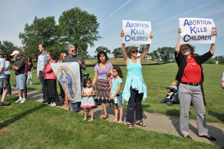 People hold pro-life signs in front of Planned Parenthood in Bettendorf, Iowa, in 2015. (CNS photo/Lindsay Steele, The Catholic Messenger)