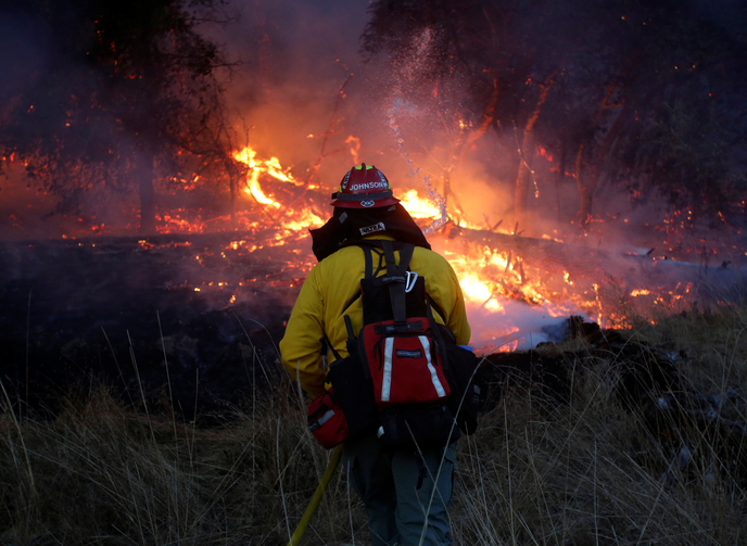 A firefighter battles a wildfire on Oct. 14 near Santa Rosa, Calif. The fire claimed the lives of more than 40 people. (CNS photo/Jim Urquhart, Reuters)