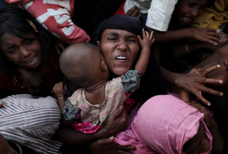 A Rohingya woman holds her infant as she scuffles to receive relief aid Nov. 28 in the Kutupalong refugee camp near Cox's Bazar, Bangladesh. (CNS photo/Susana Vera, Reuters)