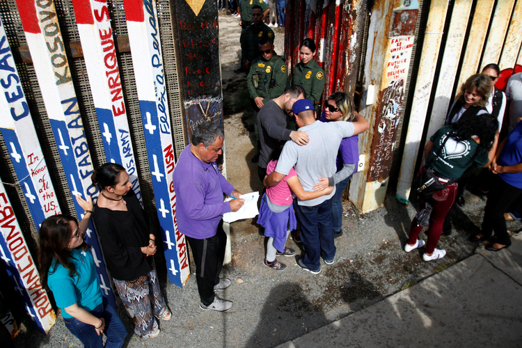 U.S. Border Patrol agents open a single gate to allow families to hug and talk on Nov. 18 along the U.S.-Mexico border in Tijuana, Mexico. (CNS photo/Jorge Duenes, Reuters)