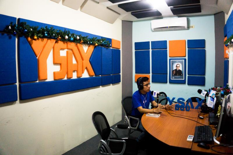 A photo of Blessed Oscar Romero is displayed as a YSAX radio volunteer works in the studio on Dec. 9 in San Salvador, El Salvador. In San Salvador's traffic jams or at work, people turn on radio YSAX to listen to Blessed Romero's homilies, just as they did over 30 years ago. (CNS photo/Melissa Vida)