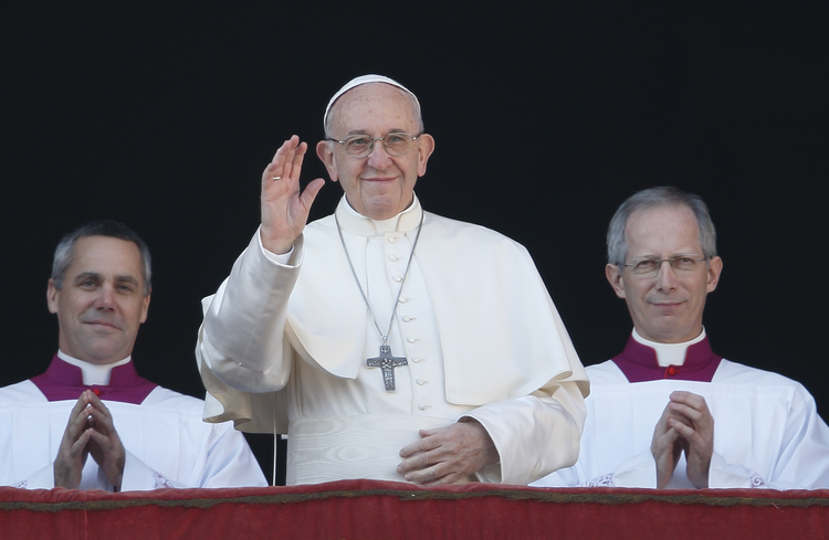 "Pope Francis waves as he arrives to deliver his Christmas message and blessing ""urbi et orbi"" (to the city and the world) from the central balcony of St. Peter's Basilica at the Vatican on Dec. 25. (CNS photo/Paul Haring)"