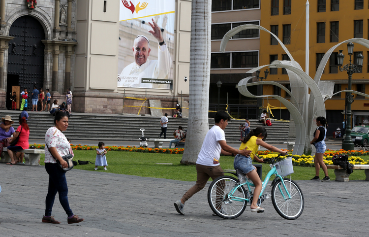 People walk near a banner with an image of Pope Francis on the facade of the cathedral in Lima, Peru, on Jan. 3. On Jan. 15, Pope Francis will begin a six-day visit to Chile and Peru. (CNS photo/Mariana Bazo, Reuters)