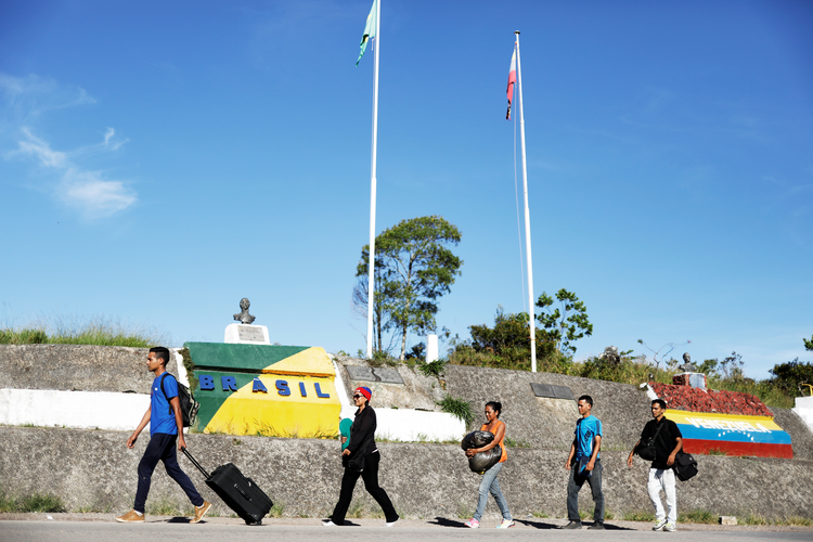 Venezuelan migrants walk across the border from Venezuela into the Brazilian city of Pacaraima. In his message for World Day of Migrants and Refugees Jan. 14, Pope Francis urged countries to welcome, protect and integrate foreigners who cross their borders. (CNS photo/Nacho Doce)
