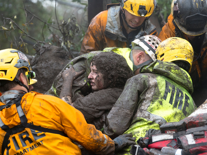 Emergency personnel carry a woman rescued from a collapsed house Jan. 9 after a mudslide in Montecito, Calif. Weeks after devastating fires tore through Southern California, heavy rains sent mudslides rolling down hillsides in Santa Barbara County, leaving at least 13 people dead and dozens injured. (CNS photo/Kenneth Song, Santa Barbara News-Press via Reuters)