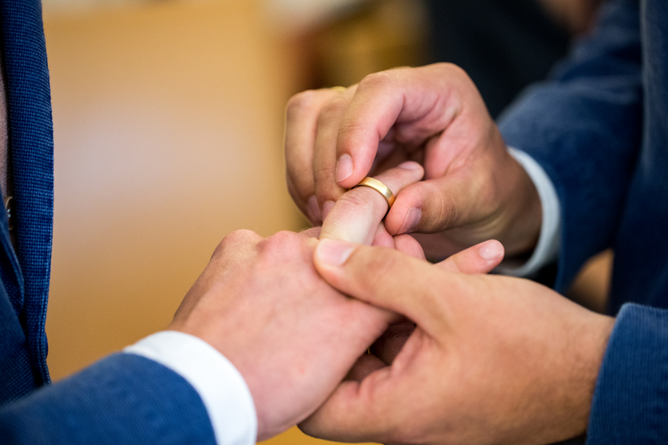 Two same-sex partners exchange wedding bands during a 2017 ceremony at the civil registry office in Munich. (CNS photo/Marc Mueller, EPA)