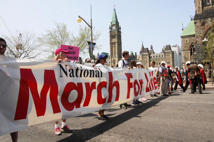 "Pro-life supporters carry a banner during the annual National March for Life in 2016 on Parliament Hill in Ottawa, Ontario. Pro-life advocates are making plans to address a new law in Ontario that will create ""bubble zones"" around abortion facilities in in Ottawa and likely force the march to find a new route. (CNS photo/Art Babych)"