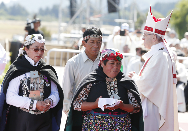 Indigenous people walk past Pope Francis after presenting offertory gifts during the pope's celebration of Mass at the Maquehue Airport near Temuco, Chile, Jan. 17. (CNS photo/Paul Haring)