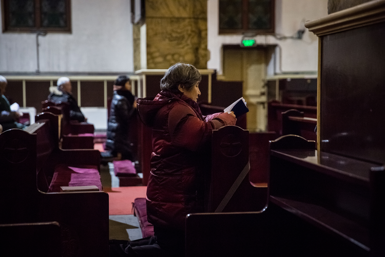 A woman prays during morning Mass on Jan. 30 in the Cathedral of the Immaculate Conception in Beijing. (CNS photo/Roman Pilipey, EPA)