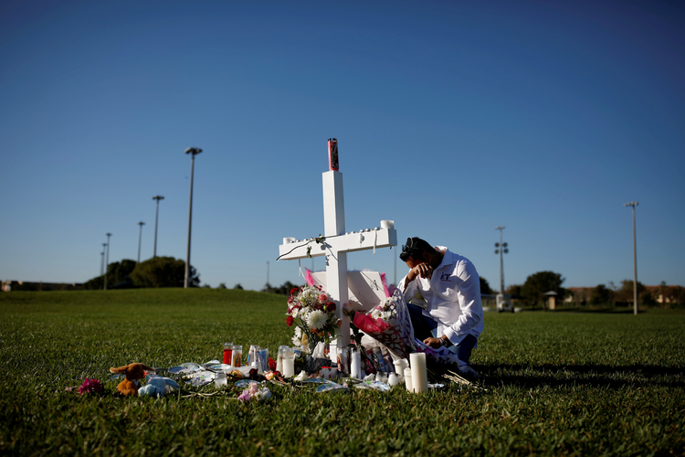 Joe Zevuloni weeps in front of a cross placed in a park to commemorate the victims of the shooting at nearby Marjory Stoneman Douglas High School in Parkland, Fla., on Feb. 16. At least 17 people were killed in the Feb. 14 shooting. (CNS photo/Carlos Garcia Rawlins, Reuters)